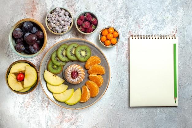 Vista dall'alto composizione di frutta diversa frutta fresca e affettata su sfondo bianco vitamina frutta dolce salute matura