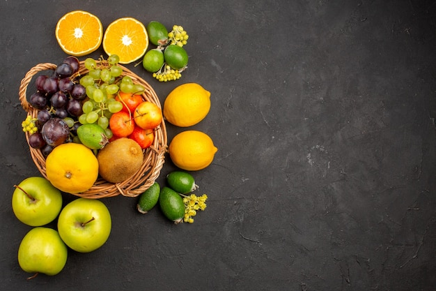 Top view different fruits composition ripe and mellow fruits on dark background diet mellow fresh fruits