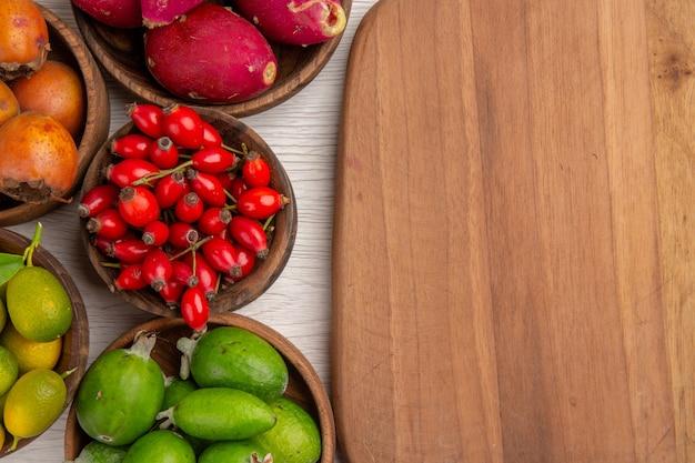 上面図さまざまな果物フェイジョアと白い背景色のプレート内の他の果物熱帯の健康エキゾチックなベリーの木熟した
