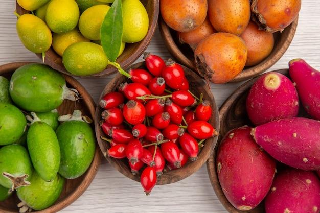 Вид сверху различных фруктов фейхоа и других фруктов внутри тарелок на белом фоне здоровья спелых экзотических ягод тропического дерева