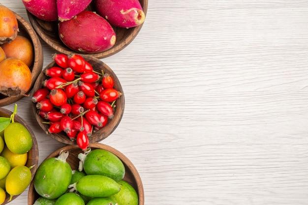 上面図さまざまな果物フェイジョアと白い背景のプレート内の他の果物熱帯の健康熟したエキゾチックなベリー色の木テキストのための無料の場所