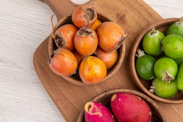 Вид сверху разных фруктов фейхоа, ягод и других фруктов внутри тарелок на белом фоне спелых продуктов экзотического цвета