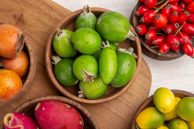 Вид сверху разные фрукты, ягоды фейхоа и другие фрукты внутри тарелок на белом столе, спелые продукты экзотического цвета