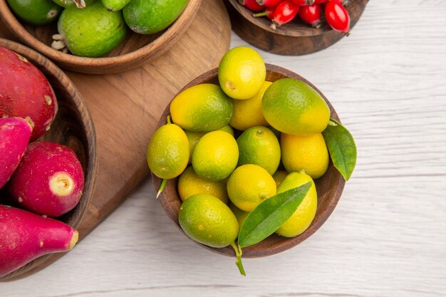 Top view different fruits feijoas berries and other fruits inside plates on white background ripe exotic  color