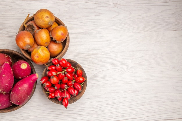 Top view different fruits feijoas and other fruits inside plates on white background health ripe exotic color tropical tree berry free place