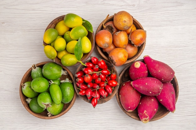 Top view different fruits feijoas and other fruits inside plates on white background health ripe exotic tropical tree berry color
