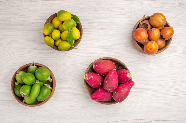 Top view different fruits feijoas and other fruits inside plates on a white background health ripe food exotic color tropical tree