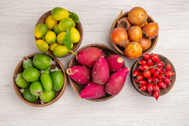 Top view different fruits feijoas and other fruits inside plates on the white background health ripe food exotic color tropical tree
