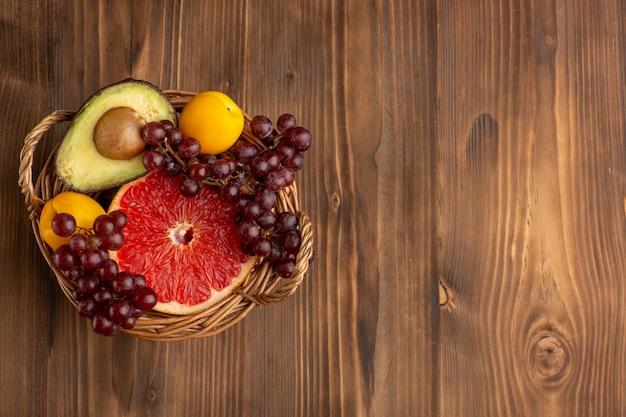 茶色の木製の机の上のバスケット内のさまざまな果物の上面図