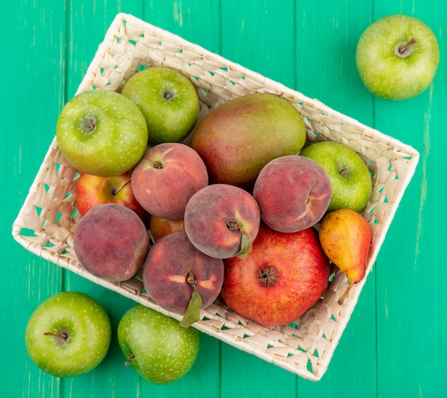 Top view of different fruits like peach mango pomegranate pear on bucket with green apples on green