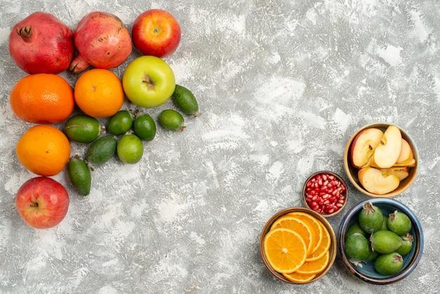 Vista dall'alto diversi frutti arance feijoa mandarini e mele su sfondo bianco mellow frutta fresca matura
