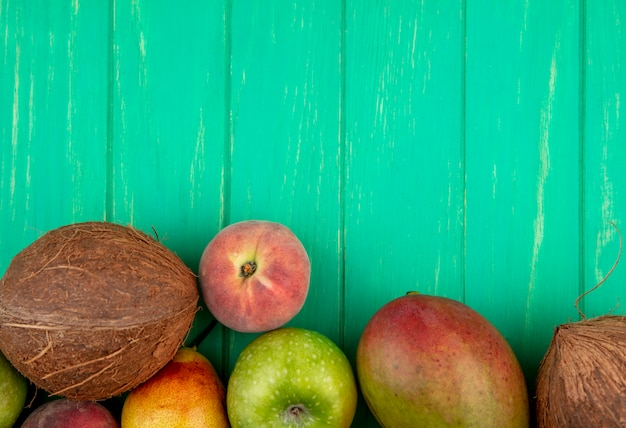 Top view of different fruits such as coconut apple peach mango on green with copy space