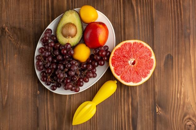 Vista dall'alto diversi frutti con pompelmo sulla scrivania in legno marrone