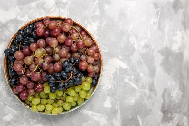 明るい白い机の上にさまざまなブドウのジューシーでまろやかな酸っぱい果物の上面図