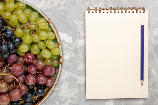 上面図白い机の上のさまざまなブドウジューシーなまろやかな酸っぱい果物