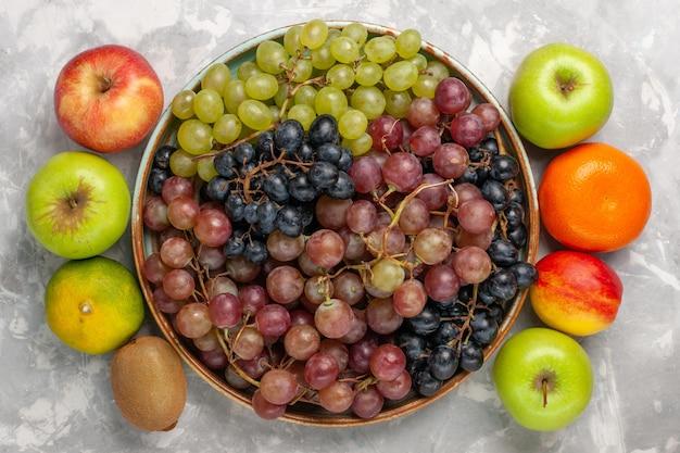 明るい白い机の上に他の新鮮な果物とさまざまなブドウの上面図
