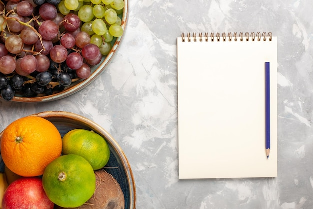 Top view different grapes with other fruits on the light white desk