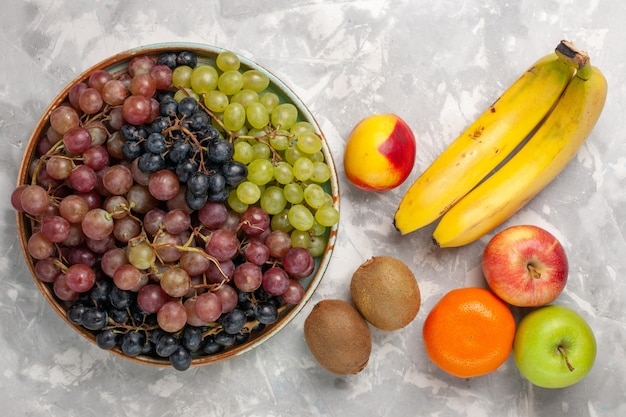 明るい白い机の上に他の果物とさまざまなブドウの上面図