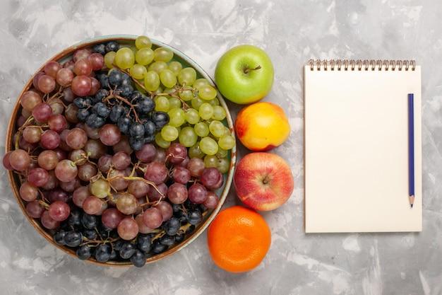 밝은 흰색 책상에 다른 과일이 있는 상위 뷰 다른 포도
