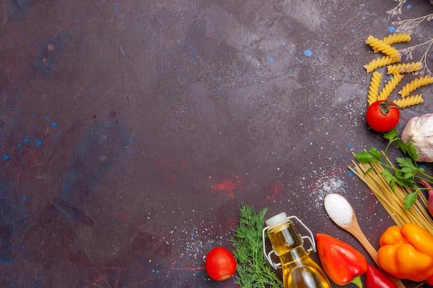 Vista dall'alto diversi ingredienti pasta cruda e verdure fresche sullo sfondo scuro prodotto alimentare salute insalata dieta