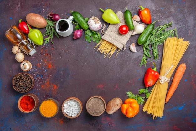 Vista dall'alto diversi ingredienti pasta cruda verdure fresche e condimenti su superficie scura prodotto pasto fresco insalata dieta salutare