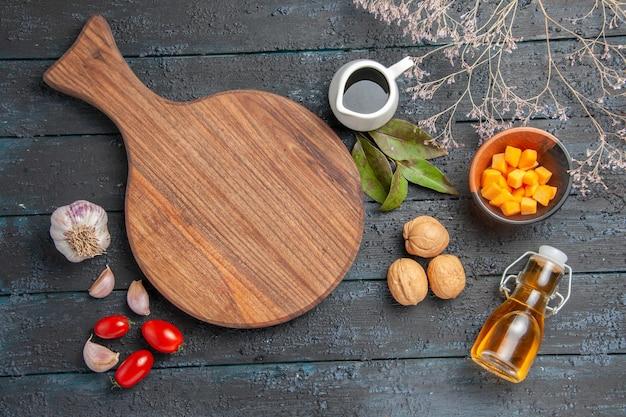 Vista dall'alto diversi ingredienti noci carota e aglio sulla scrivania scura colore cibo insalata matura