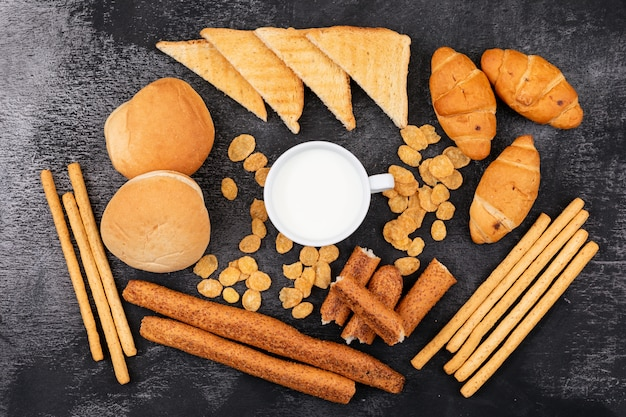 Top view of different kind of bread as crackers, toasts, croissants and milk