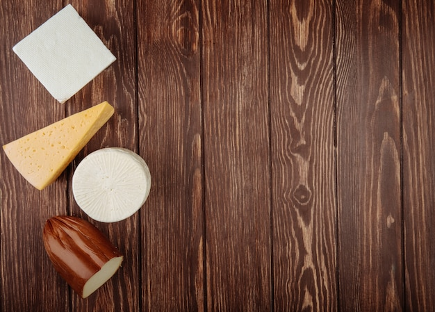 Top view of different kind of cheese on rustic wooden table with copy space