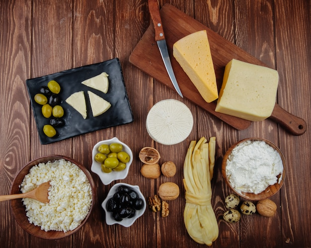 Top view of different kind of cheese on wooden cutting board , cottage cheese in bowls with pickled olives and walnuts on dark rustic table