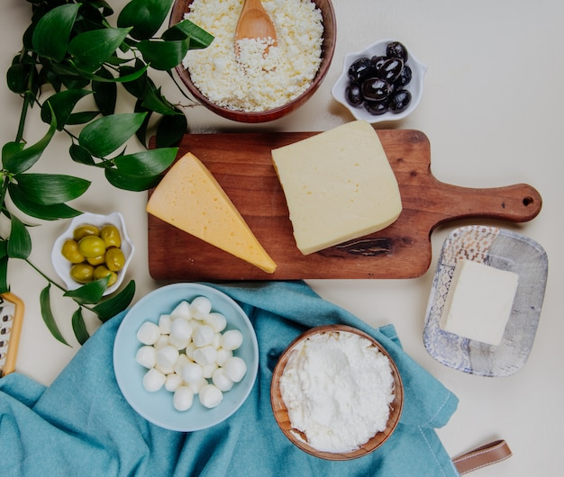 Top view of different kind of cheese on wooden cutting board and cottage cheese in a wooden bowl with pickled olives on rustic table