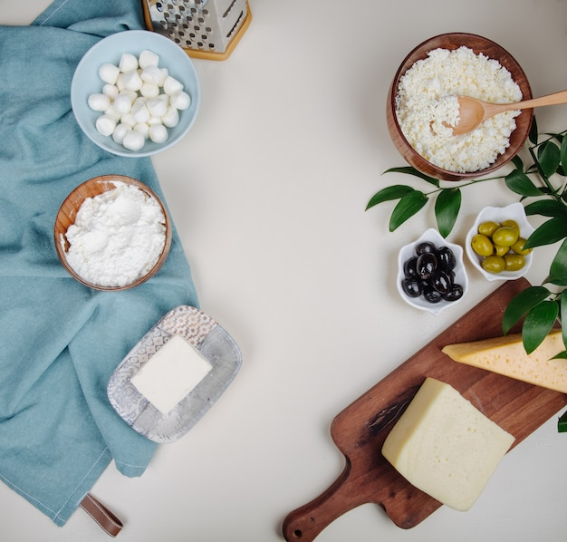 Top view of different kind of cheese on wooden cutting board and cottage cheese in a wooden bowl with pickled olives on white table