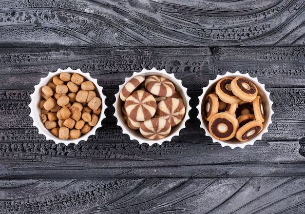 Top view of different kind of snacks as coockies and crackers in bowls on dark  horizontal