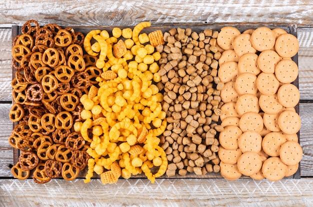 Vista superiore del tipo differente di spuntini come cracker e biscotti sull'orizzontale di legno bianco
