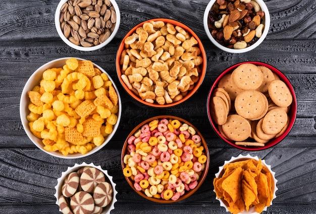 Vista superiore di diversi tipi di snack come noci, cracker e biscotti in ciotole su superficie scura orizzontale