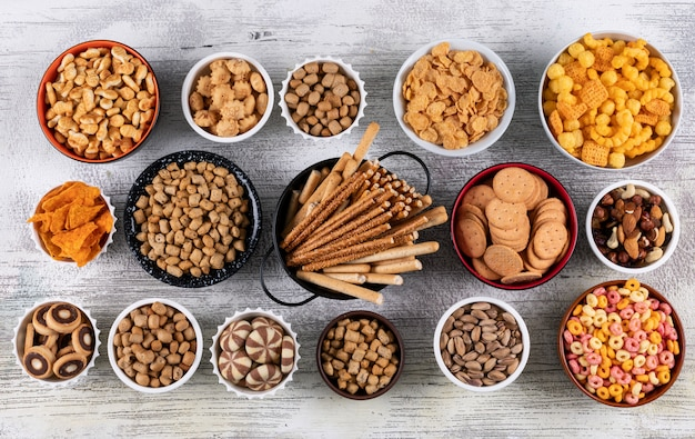 Top view of different kind of snacks as nuts, crackers and cookies in bowls on white wooden surface horizontal