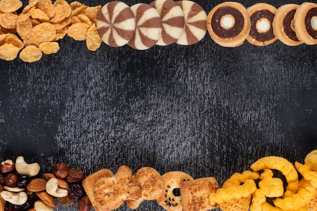 Top view of different kind of snacks as nuts, crackers and cookies with copy space on dark background horizontal
