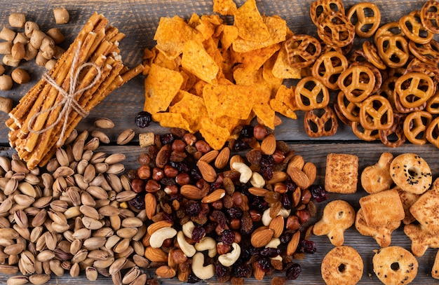 Top view of different kind of snacks as nuts, crackers and cookies with copy space on dark wooden surface horizontal