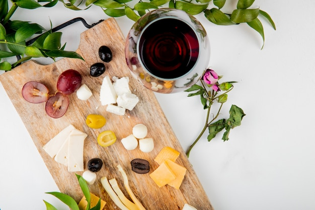 Top view of different kinds of cheese with grape pieces olives on cutting board with red wine on white decorated with flowers and leaves with copy space 1