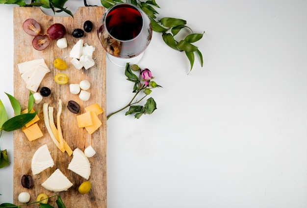 Top view of different kinds of cheese with grape pieces olives on cutting board with red wine on white decorated with flowers and leaves with copy space