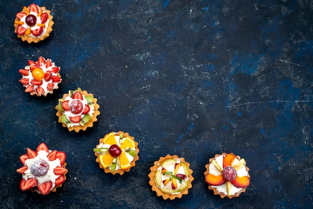 A top view different little cakes with cream and fresh sliced fruits on the blue backgound fruit cake biscuit