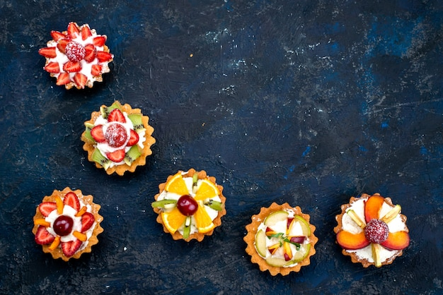 A top view different little cakes with cream and fresh sliced fruits on the blue backgound