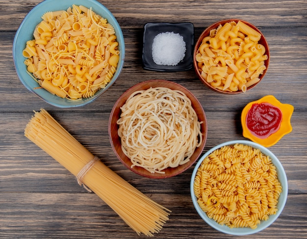 Top view of different macaronis as spaghetti rotini vermicelli and others with salt and ketchup on wood
