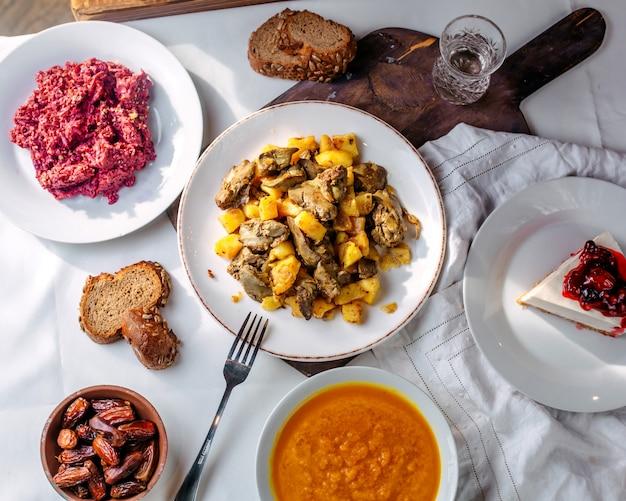 Вид сверху различных блюд, таких как жареный мясной салатный суп и кусочек торта на белом полу