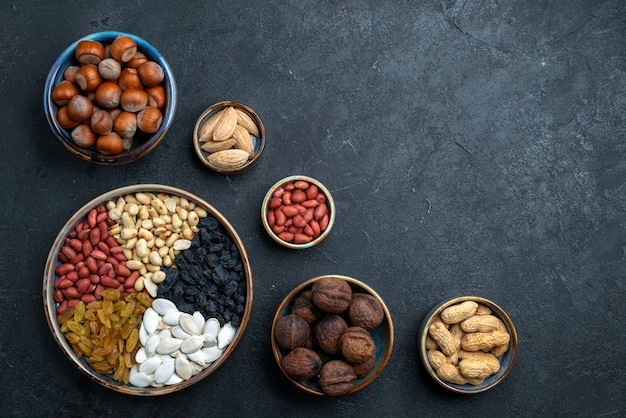 Top view different nuts composition of snacks on dark-grey background nuts snack photo walnut hazelnut