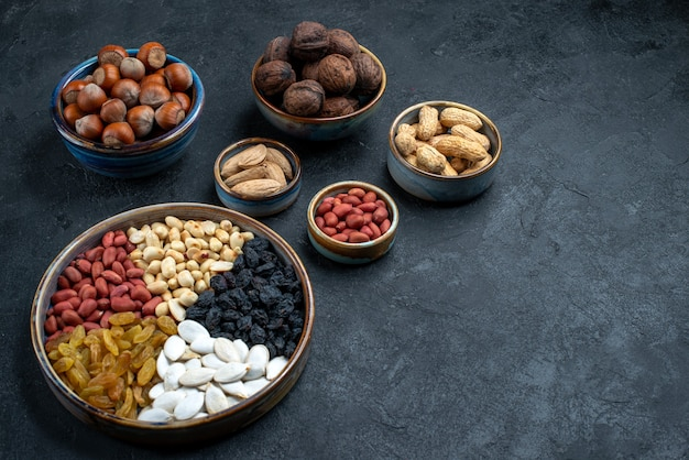 Top view different nuts composition of snacks on dark-grey background nuts snack photo walnut hazelnuts