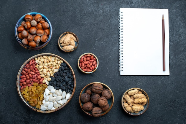 Top view different nuts composition of snacks with notepad on dark-grey background nut snack photo walnut hazelnut