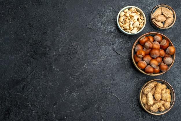 Вид сверху разные орехи, фундук и арахис на сером фоне, ореховая закуска, грецкий орех, пищевой завод