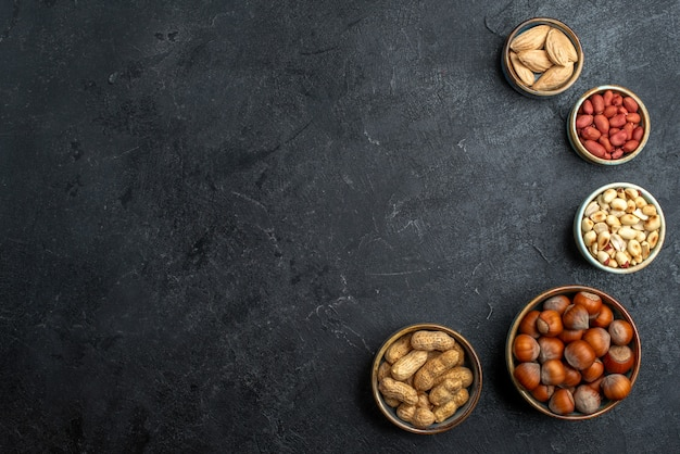 Top view different nuts hazelnuts and peanuts on grey background nut snack walnut food plant