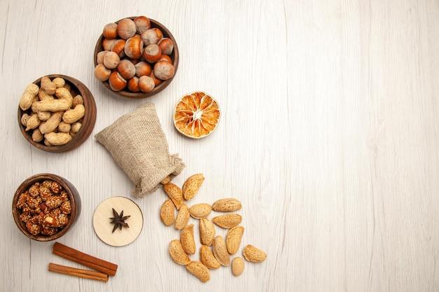 白い机の上の小さな鍋の中のさまざまなナッツの上面図ナッツスナッククルミヘーゼルナッツ