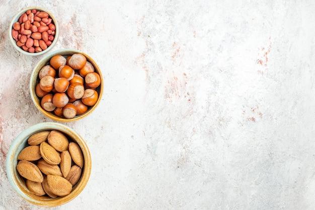 Vista dall'alto diversi dadi all'interno di piccoli vasi sullo sfondo bianco spuntino dado noce fresca nocciola arachidi